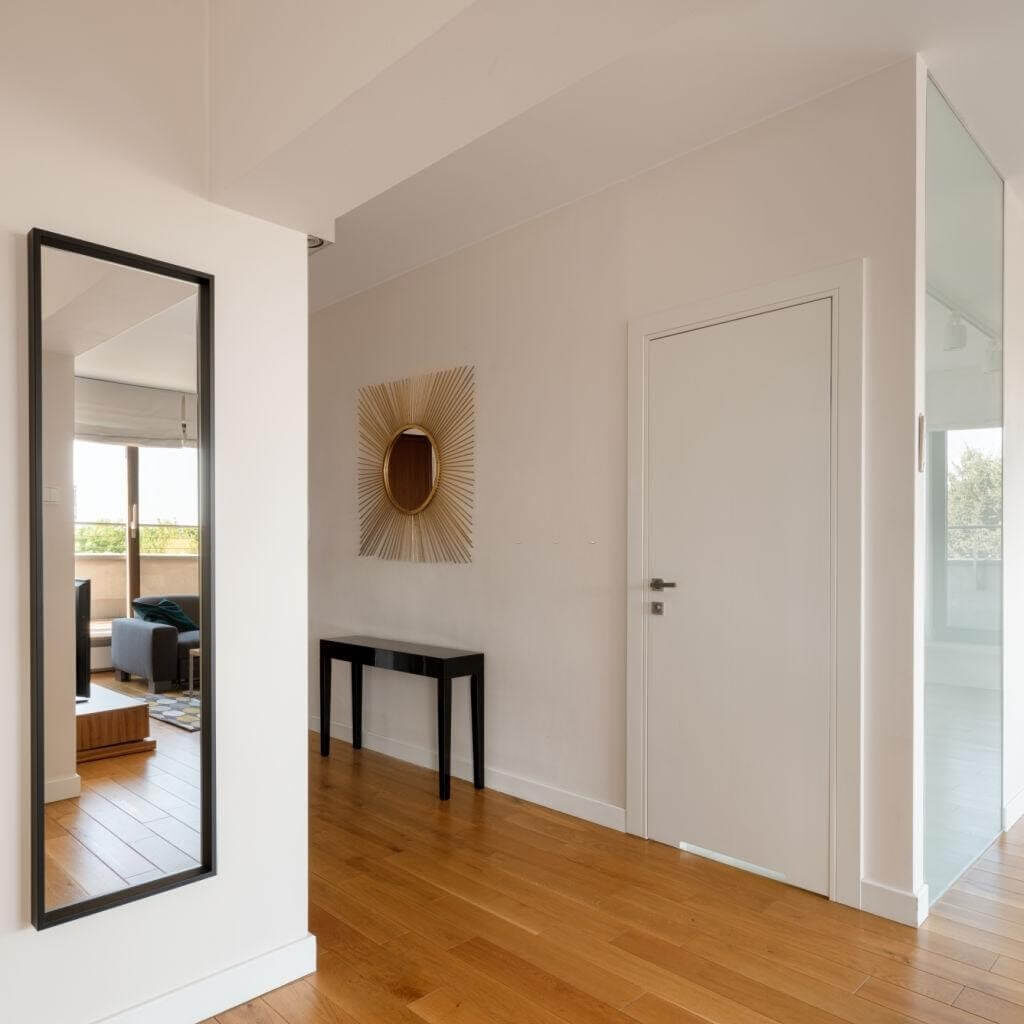 A full-length mirror on the entrance and staircase wall