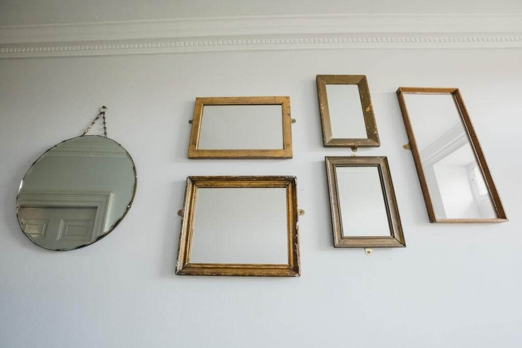 A gallery with different shapes and sizes of mirrors